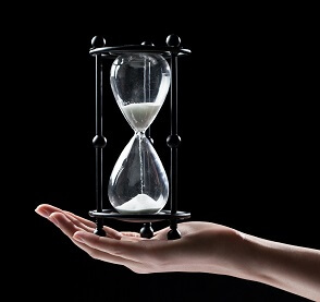 Hand holding a sand watch hourglass over black background