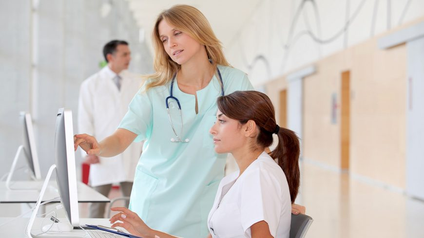 Nurse with intern working in front of computer