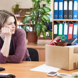 Young worker with regret looking at box with personal belongings on table