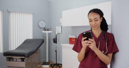 Black woman nurse texting on smartphone